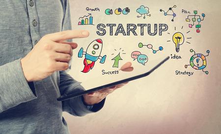 Jonge man wijzend op Startup concept over een tablet-computer