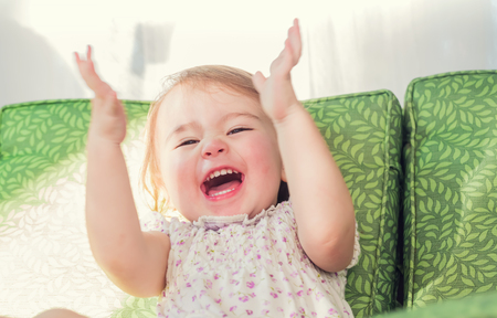 미소하고 그녀의 손을 박수 행복 유아 소녀