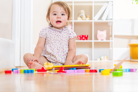 babies playing: Happy toddler girl smiling and playing with toy blocks inside her house