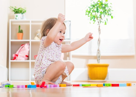 Happy toddler girl smiling while playing with her wooden toy blocks Фото со стока
