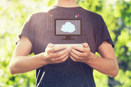 Cloud Computing concept with young man holding his smartphone outside in the park toward sunset