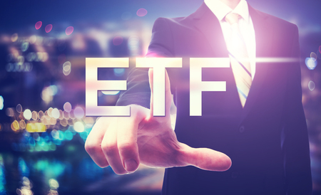 traded: Businessman pointing at ETF on blurred city background Stock Photo