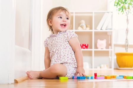 Happy toddler girl with a big smile playing with wooden toy blocks inside her house Stock Photo