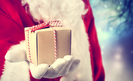 to santa: Santa Claus holding a gift on his hand Stock Photo