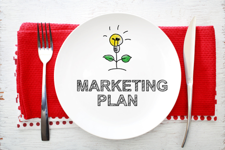 napkins: Marketing Plan concept on white plate with fork and knife on red napkins
