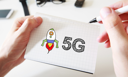 5g: Mans hand drawing 5G concept on white notebook Stock Photo