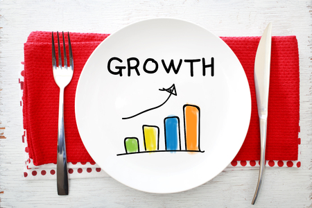 napkins: Growth concept on white plate with fork and knife on red napkins