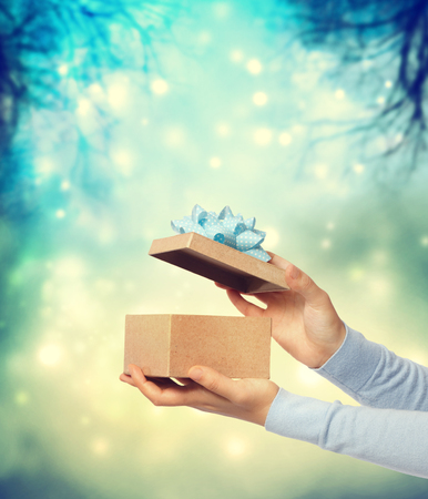 gift bow: Woman holding and presenting a gift box on teal winter background