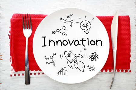 Innovation concept on white plate with fork and knife on red napkins