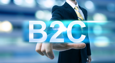 b2c: Businessman pointing at B2C (business to consumer) on blurred city background