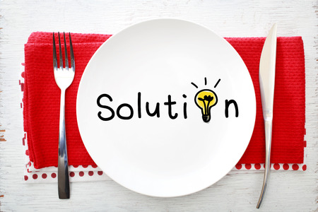 napkins: Solution concept on white plate with fork and knife on red napkins