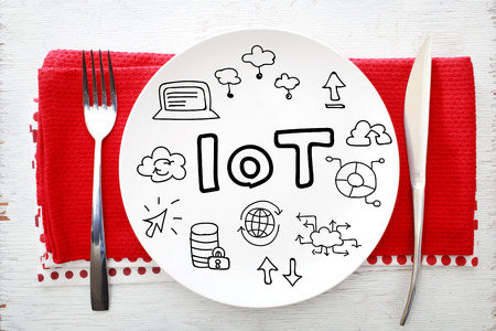 napkins: IOT - Internet of Things concept on white plate with fork and knife on red napkins Stock Photo