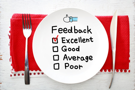 napkins: Feedback concept on white plate with fork and knife on red napkins Stock Photo