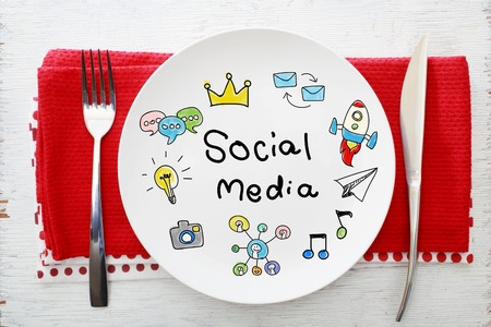 napkins: Social Media concept on white plate with fork and knife on red napkins Stock Photo