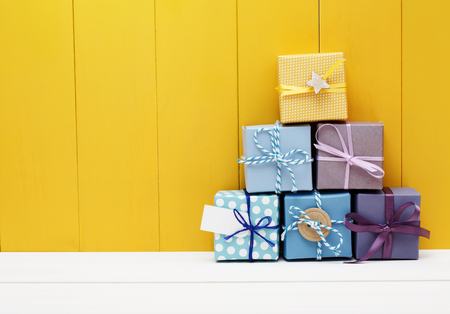 Stack of little present boxes on yellow wooden wall