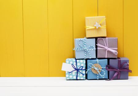 Pila di piccole scatole presenti sulla parete di legno di colore giallo Archivio Fotografico - 45656439