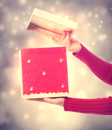 apertura: Woman holding a red gift box on bright holiday lights background