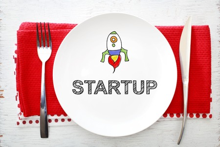 white plate: Startup concept on white plate with fork and knife on red napkins