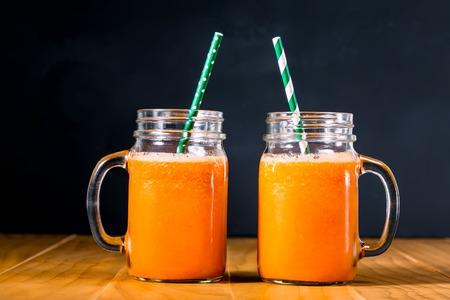 jugo de frutas: El jugo de zanahoria en albañiles tarros en negro