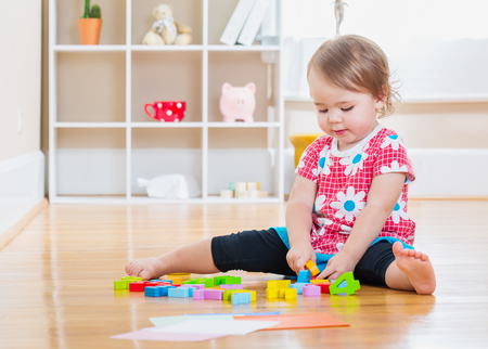 baby playing: Happy toddler girl smiling and playing with wooden toy blocks inside her house