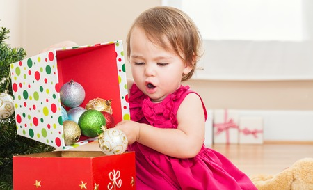 christmas decorations: Little toddler girl playing with Christmas decorations