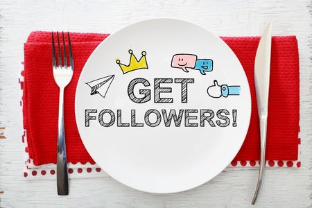 followers: Get Followers concept on white plate with fork and knife on red napkins
