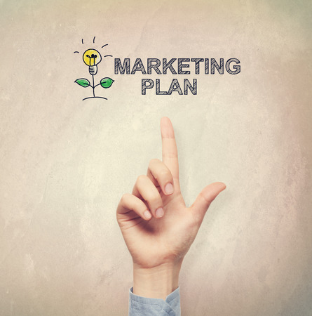 cartoon light bulb: Hand pointing to Marketing Plan concept on light brown wall background Stock Photo