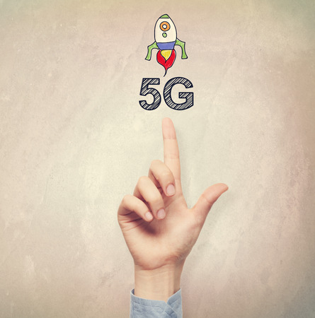5g: Hand pointing to 5G concept on light brown wall background