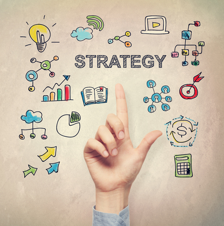 strategies: Hand pointing to Strategy concept on light brown wall background Stock Photo