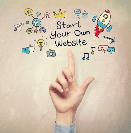 your point: Hand pointing to Start Your Own Website concept on light brown wall background