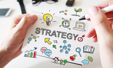 Mans hand drawing Strategy concept on white notebook