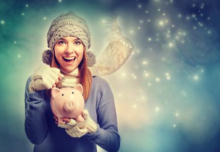 banco dinero: Mujer joven feliz que depositar dinero en su hucha rosa Foto de archivo