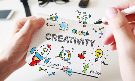 notebook: Mans hand drawing Creativity concept on white notebook Stock Photo
