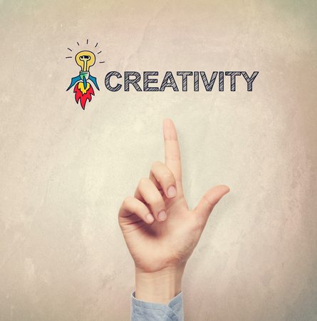 filtered: Hand pointing to Creativity concept on light brown wall background Stock Photo