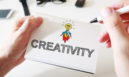 creativity concept: Mans hand drawing Creativity concept on white notebook Stock Photo