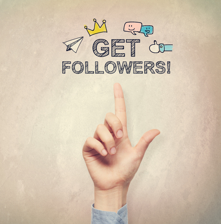 followers: Hand pointing to Get Followers concept on light brown wall background Stock Photo