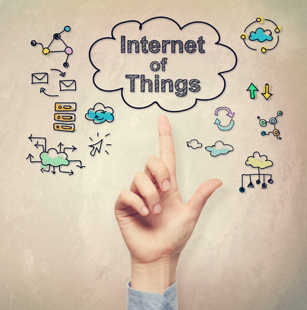 filtered: Hand pointing to Internet of Things concept on light brown wall background
