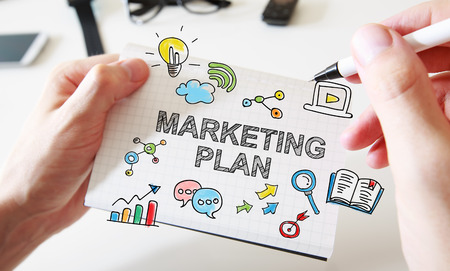 Mans hand drawing Marketing Plan concept on white notebook Standard-Bild