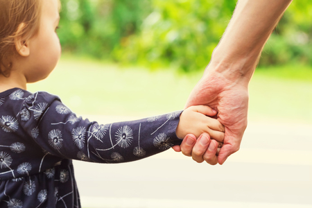 mixed race girl: Toddler girl holding hands with her father outside