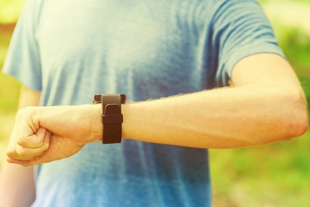 looking at watch: Male runner looking at his smart watch outside at sunset