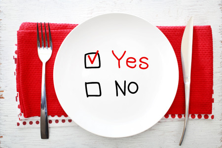 Yes or No concept on white plate with fork and knife on red napkins