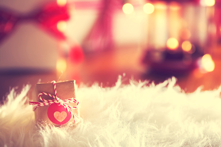samll: Small Christmas gift with heart tag on white carpet at night Stock Photo