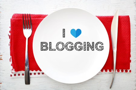 love strategy: I love Blogging concept on white plate with fork and knife on red napkins