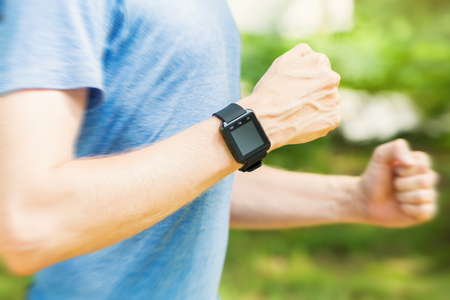 Male runner jogging outside with his smart watch at sundown