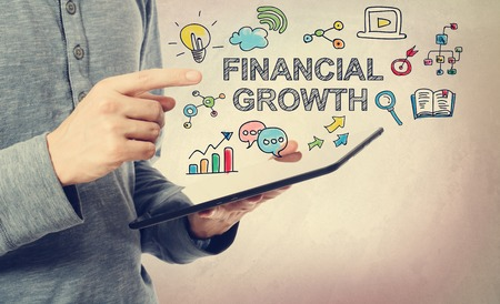 financial growth: Young man pointing at Financial Growth concept over a tablet computer