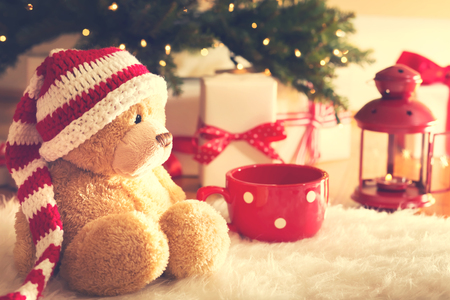 夜クリスマス ギフト ボックス白いカーペットの上でサンタの帽子を着ている熊