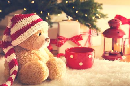 osos navide�os: Oso con el sombrero de Santa con cajas de regalo de Navidad en una alfombra blanca en la noche Foto de archivo