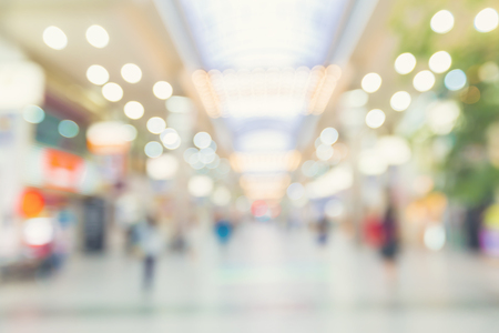 Defocused shopping mall interior with people walking at night