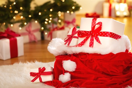 christmas decor: Christmas gift boxes in Santas sack on a white carpet at night