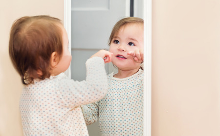 Happy peuter meisje op zoek naar zichzelf in de spiegel in haar huis Stockfoto